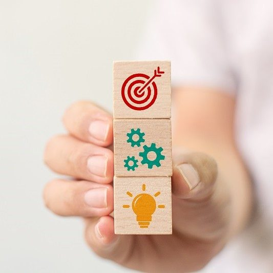 Concept of business strategy and action plan. Hand holding wood cube block stacking with icon
